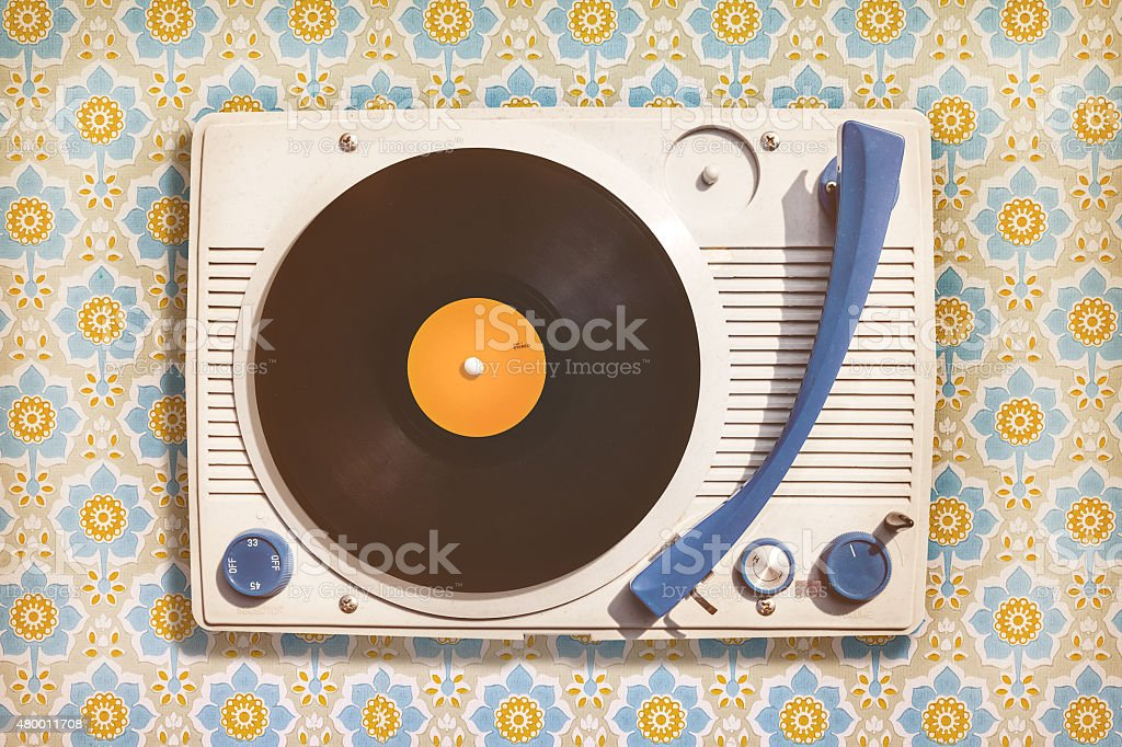 Vintage record player on top of flower wallpaper stock photo