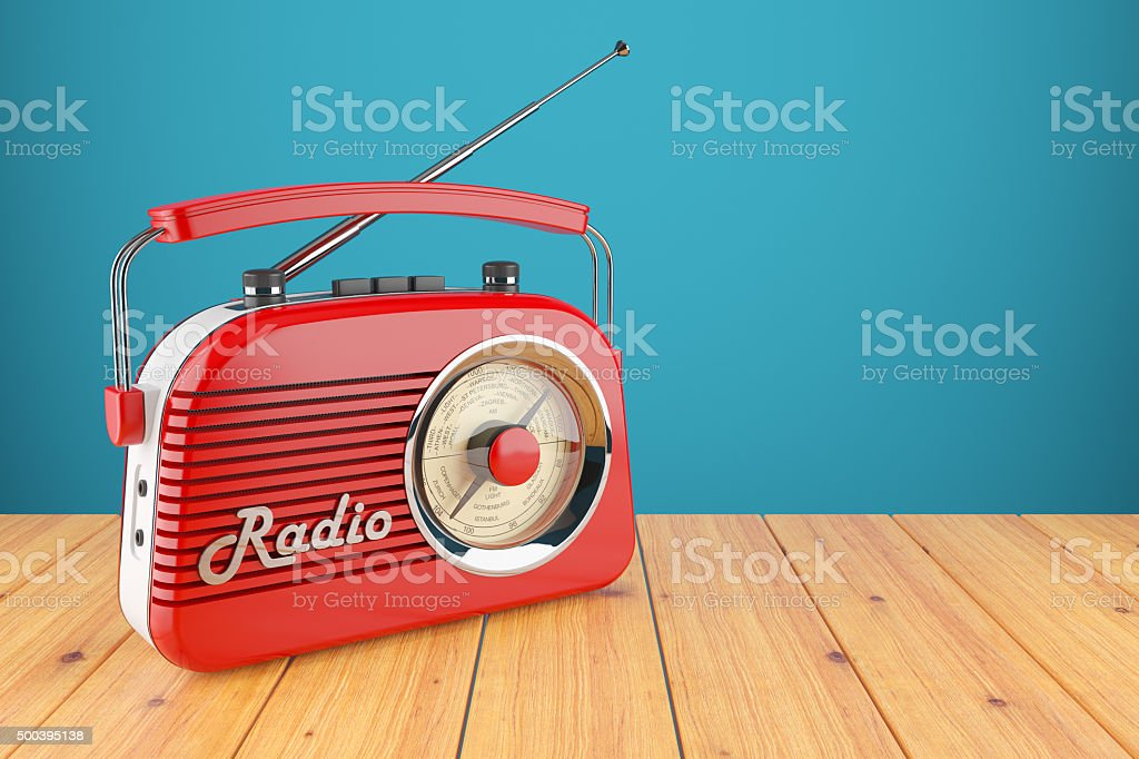 Vintage red radio receiver on wood table stock photo