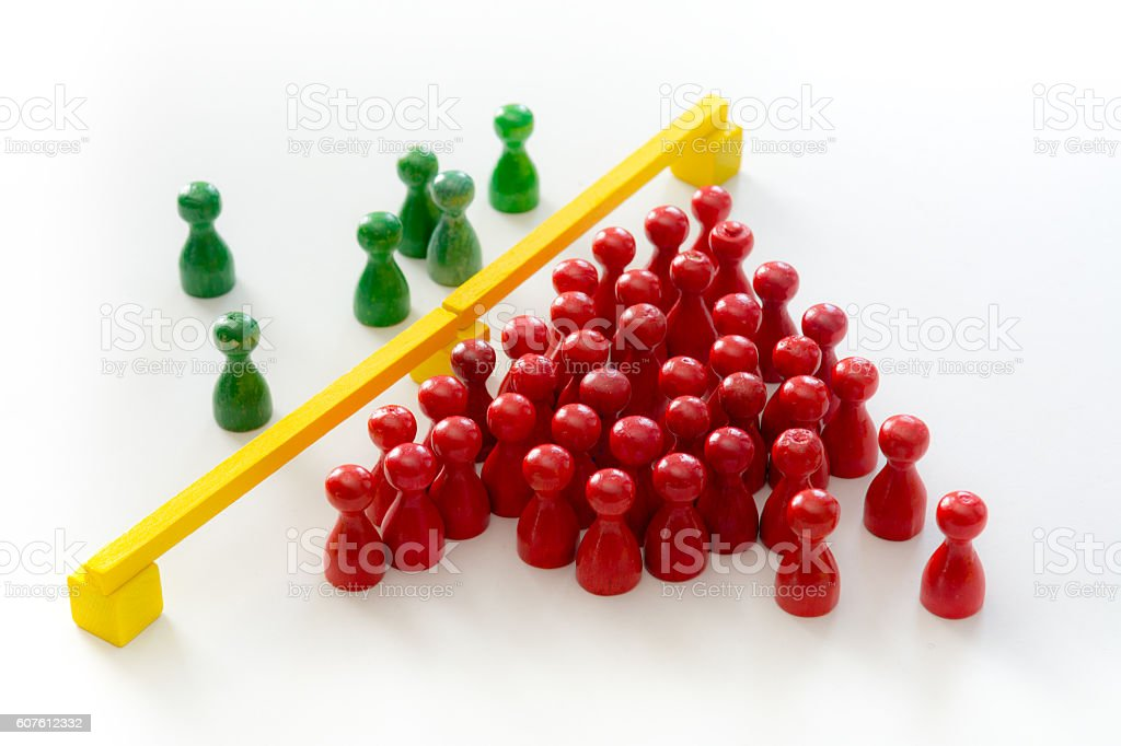 vintage red wooden pawns at one side of the border stock photo