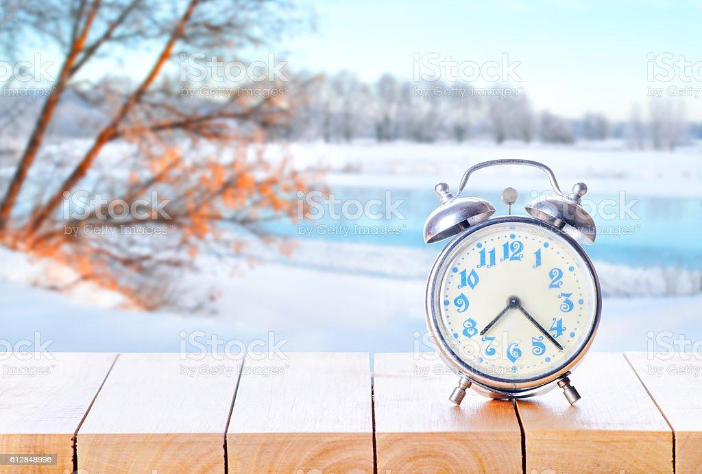 Vintage retro alarm clock on wooden table. stock photo