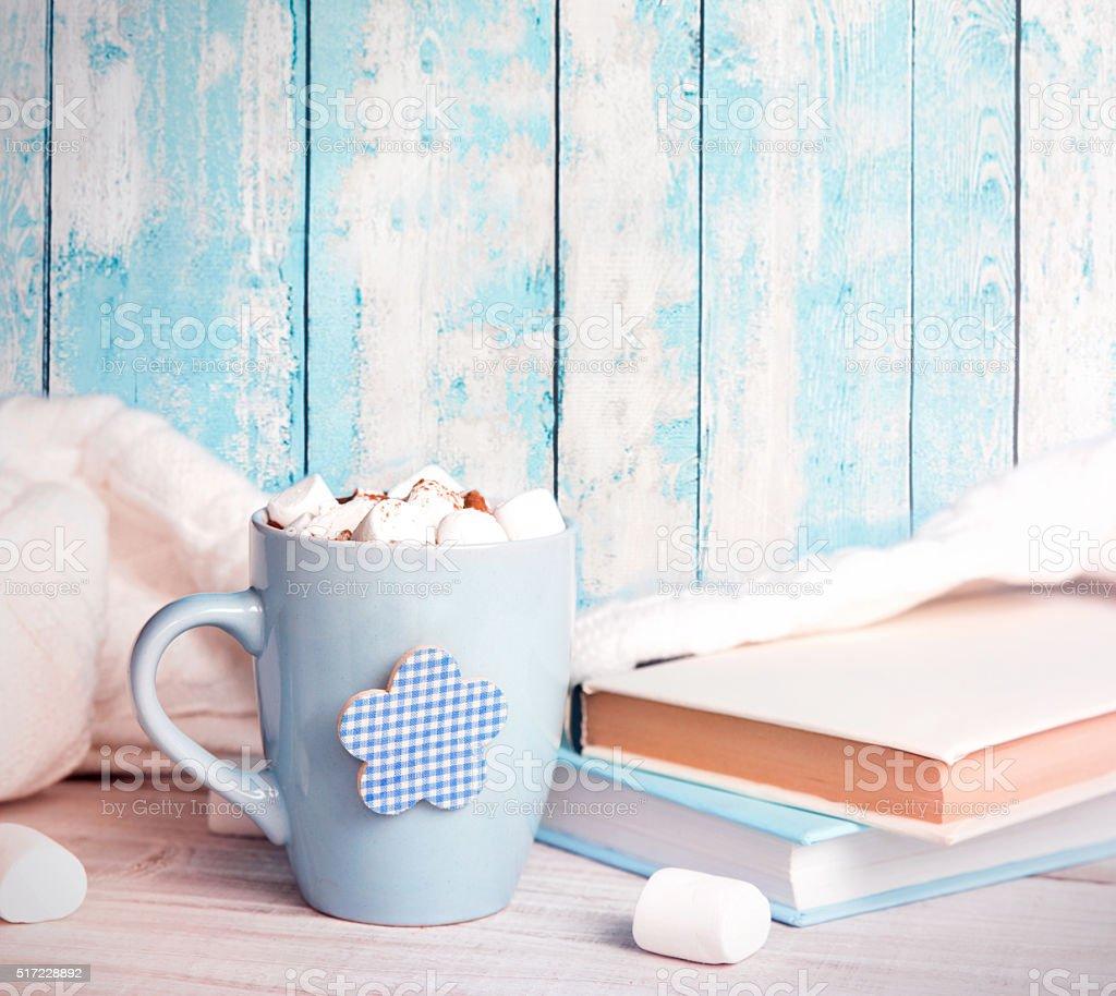 Vintage retro mug stack books on blue wooden background. stock photo