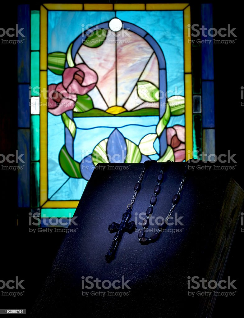 Vintage Rosary on Book with Stained Glass stock photo