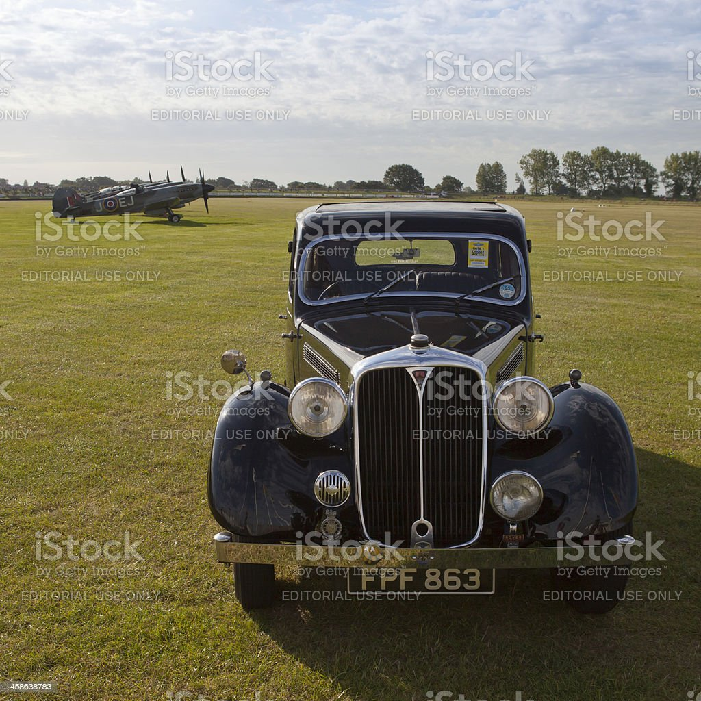 Vintage Rover 16 car and a row of Spitfire aircraft stock photo