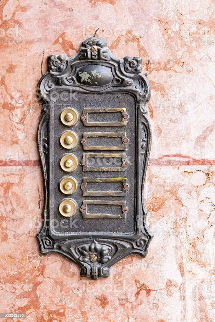 Vintage rusty doorbells on a marble wall stock photo