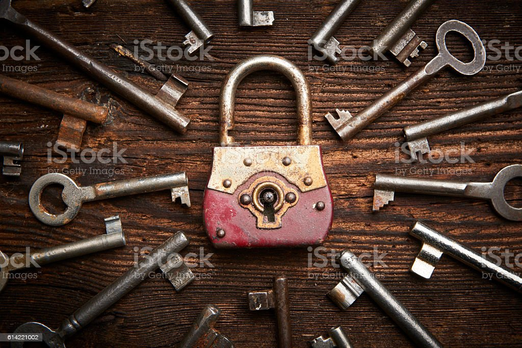Vintage rusty padlock surrounded by old keys stock photo