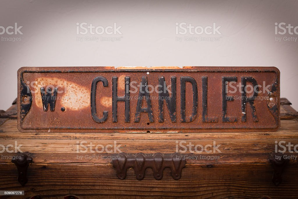 Vintage Rusty W. Chandler Street Sign on Wooden Trunk stock photo