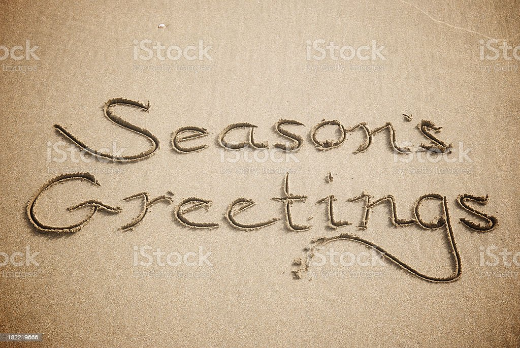 Vintage Season's Greetings Text in Sand royalty-free stock photo