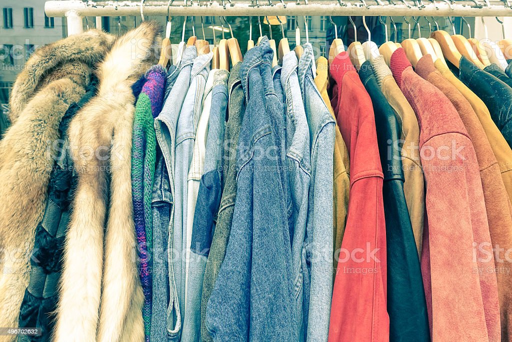 Vintage second hand clothes on shop rack at flea market stock photo