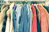Vintage second hand clothes on shop rack at flea market