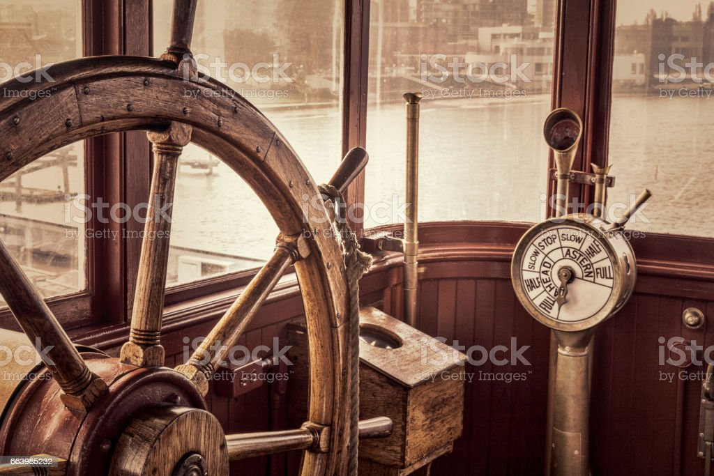 vintage ship steering wheel in sepia toning stock photo