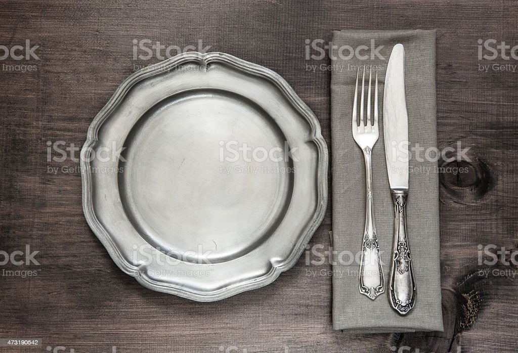 Vintage silverware A knife and a fork next to a plate  stock photo