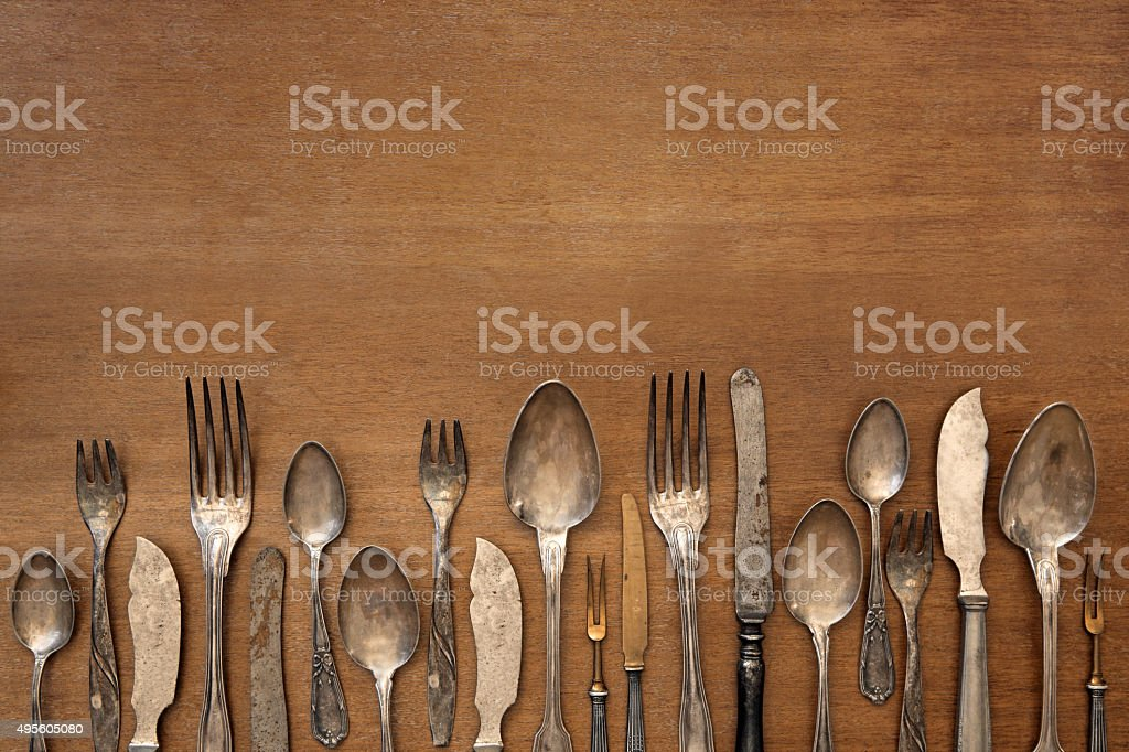 Vintage silverware aligned on a wooden table, with copy space stock photo