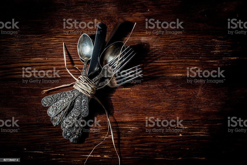 Vintage silverware on old wood table background from above stock photo
