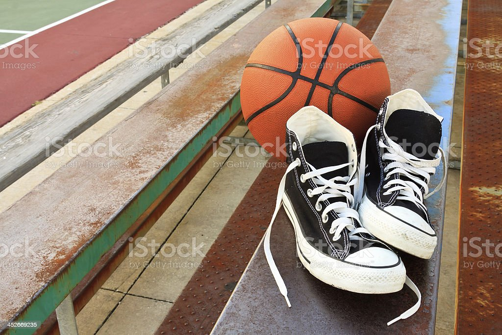 Vintage Sneakers And Basketball On Bleachers of Inner City Schoolyard stock photo