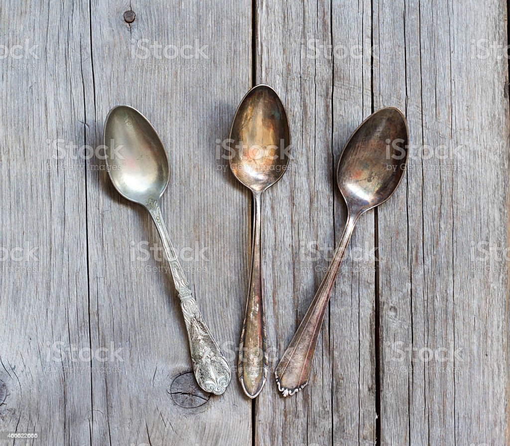 Vintage spoons with patina on wood stock photo