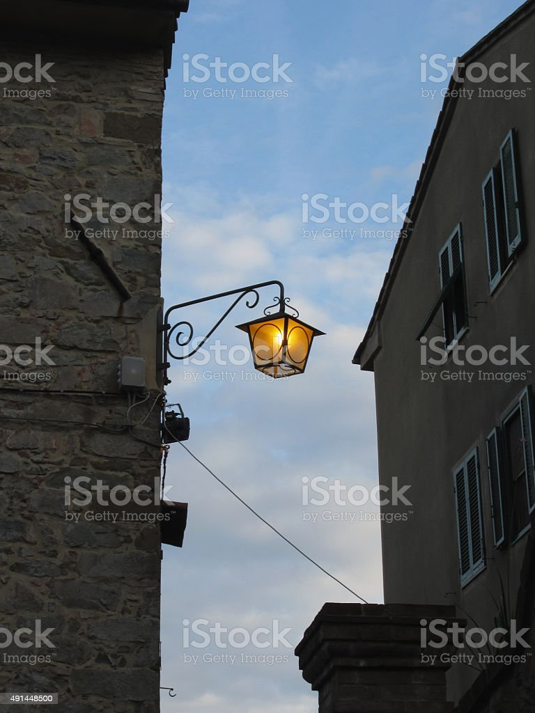 Vintage street lamp in medieval village at twilight. Tuscany, Italy stock photo