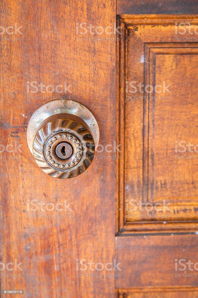 Vintage style door handle on natural wooden door. stock photo