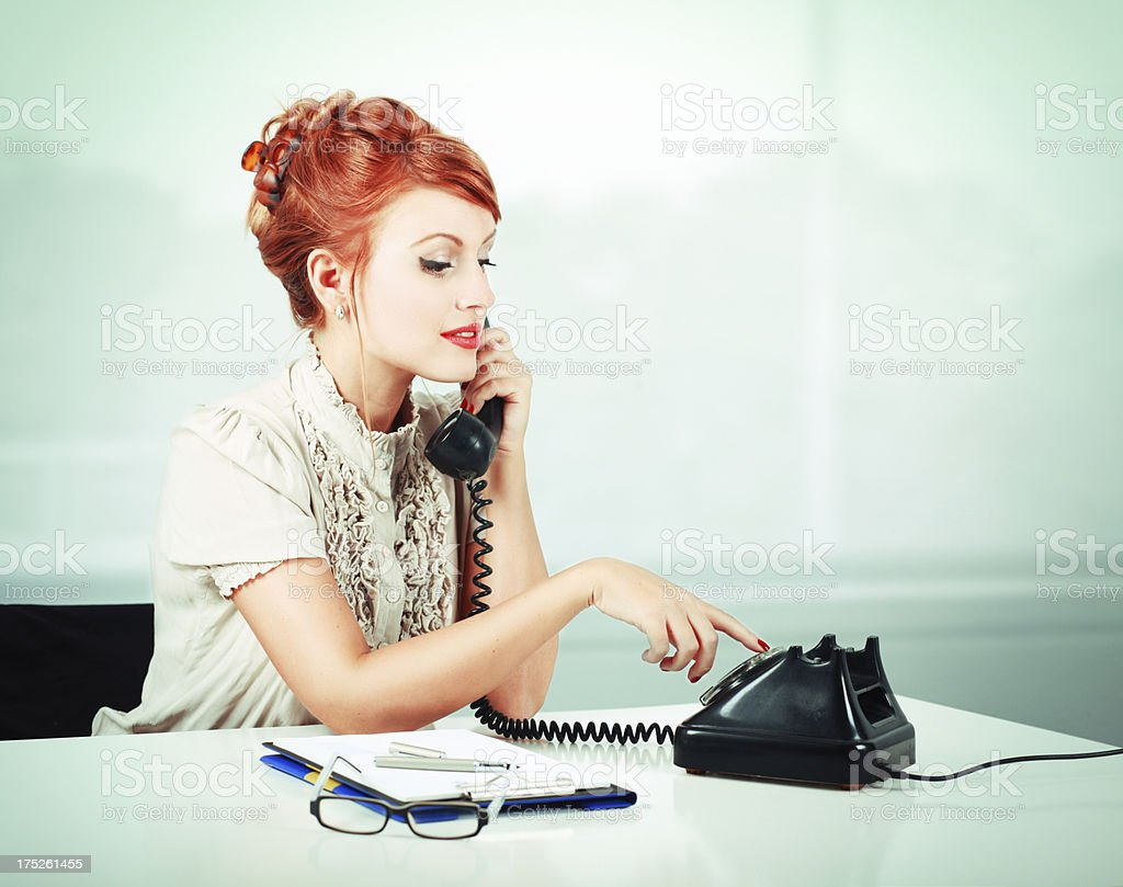 Vintage style young girl in office, making a phonecall royalty-free stock photo