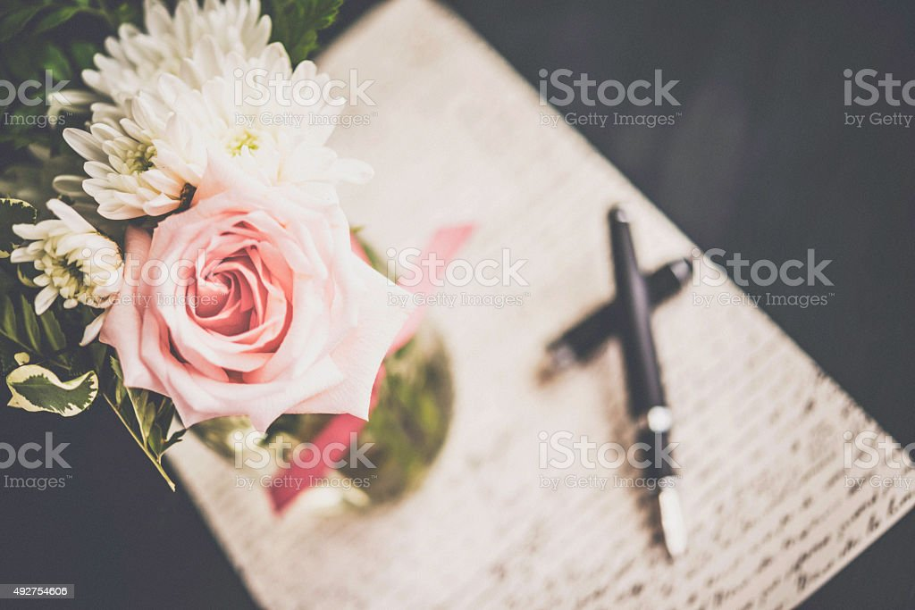 Vintage styled rose bouquet with love letter and fountain pen stock photo