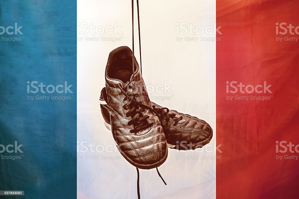vintage styled soccer shoes hanging in front of  french flag stock photo