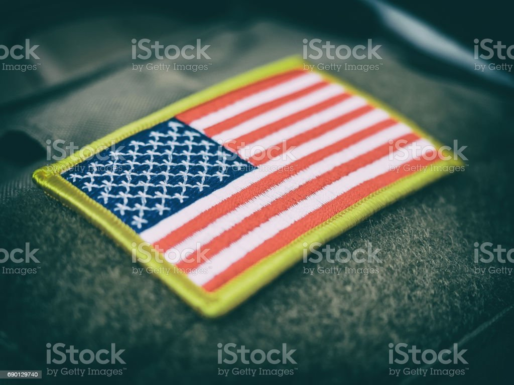 Vintage stylized USA flag patch on military bulletproof vest, shallow depth of field stock photo