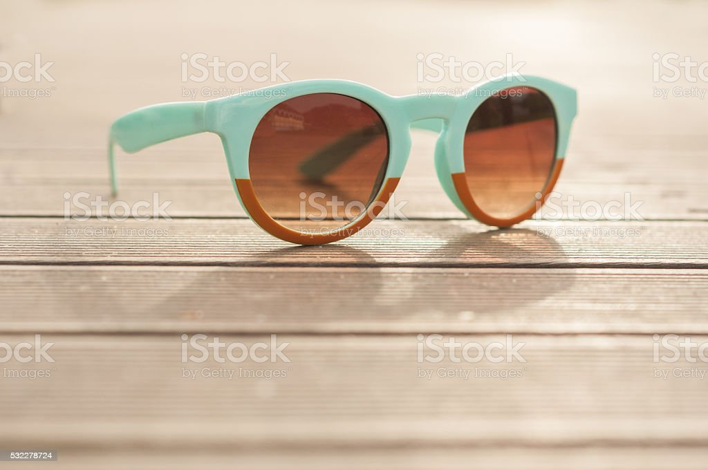 Vintage sunglasses on wooden desk outside in closeup view stock photo