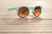 Vintage sunglasses on wooden desk outside in closeup view
