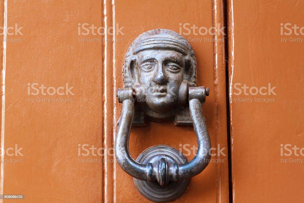 Vintage Sunlit Door Knocker on Orange Door, Sicily (Close-Up) stock photo
