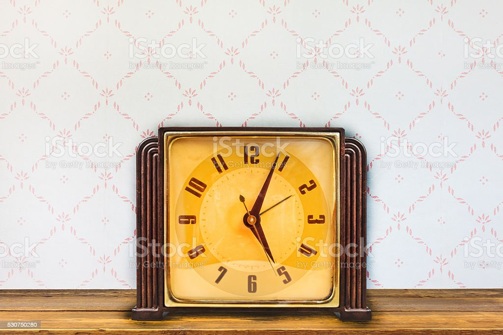 Vintage table clock in front of retro wallpaper stock photo