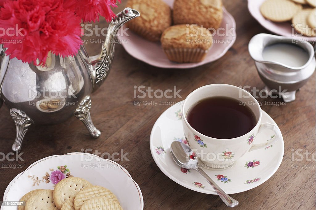 Vintage tea table setting with muffins, cookies and tea stock photo