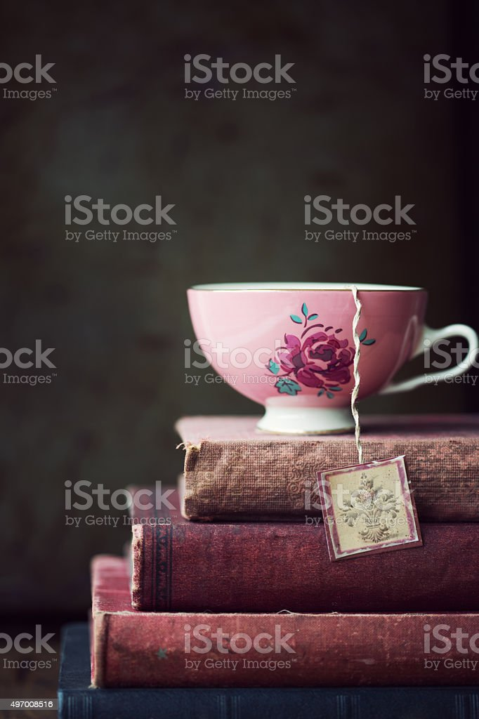 Vintage teacup on stack of old books stock photo