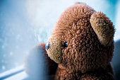 Vintage teddy bear looking through  wet window