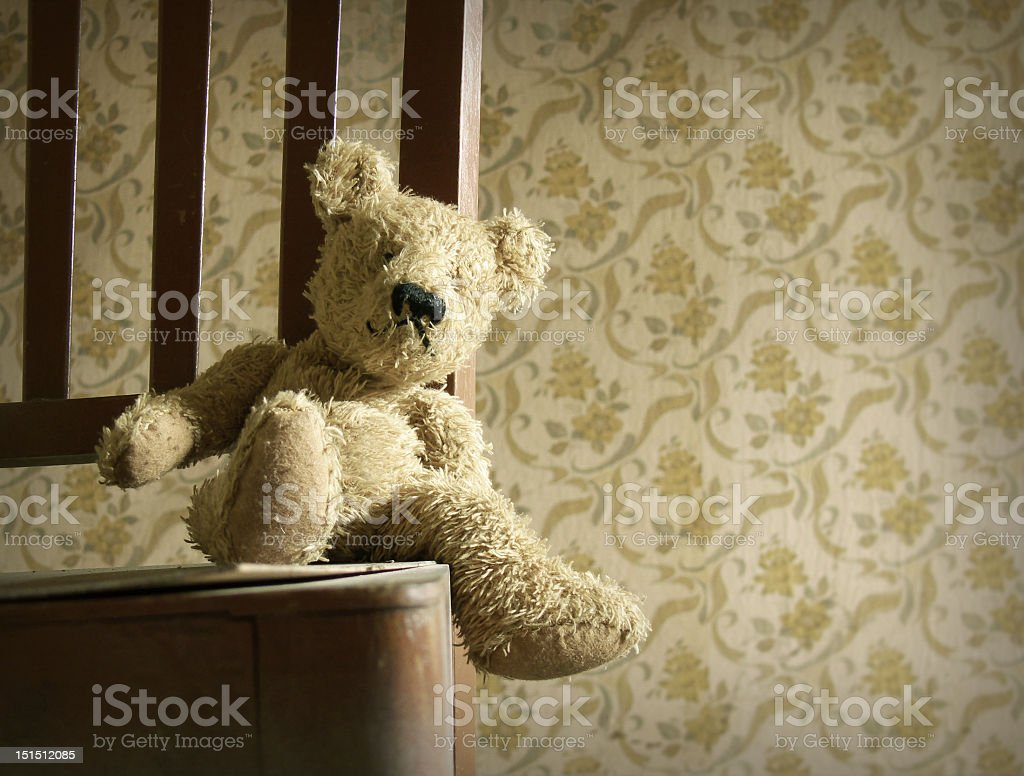 Vintage teddy bear on chair with dated wallpaper stock photo