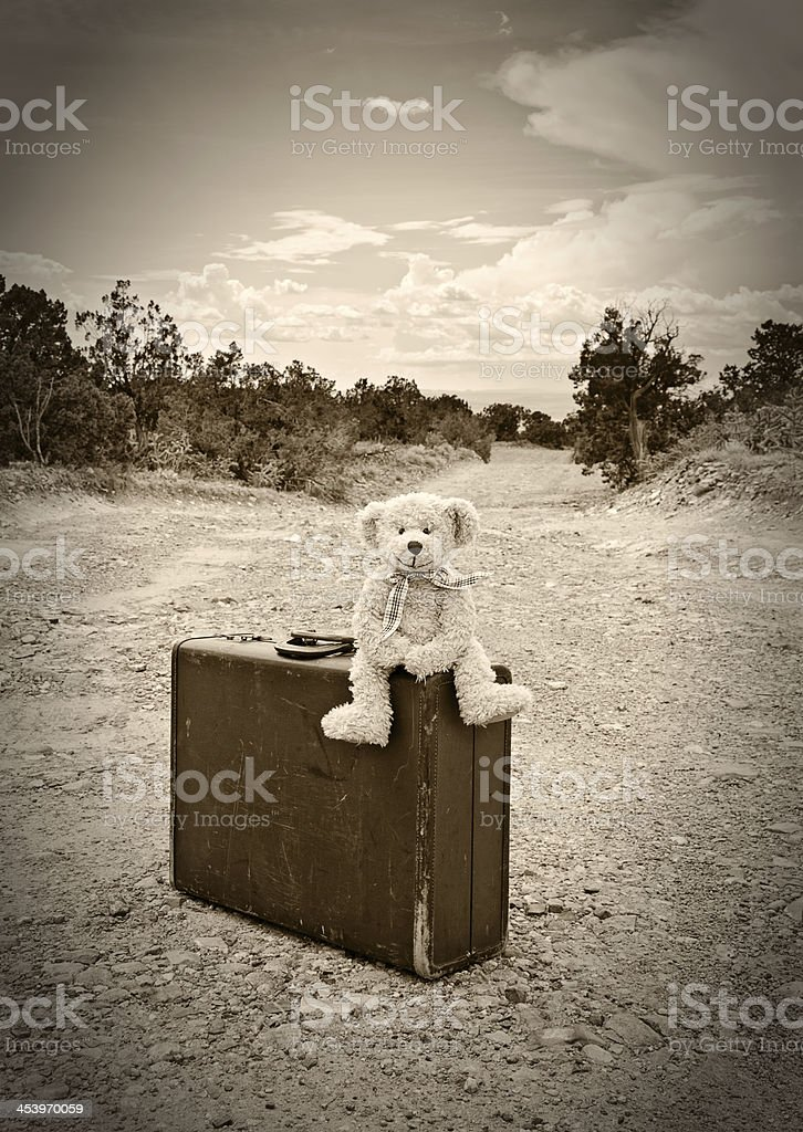 Vintage Teddy Bear Travelling, Old Suitcase on Dirt Road, Sepia royalty-free stock photo