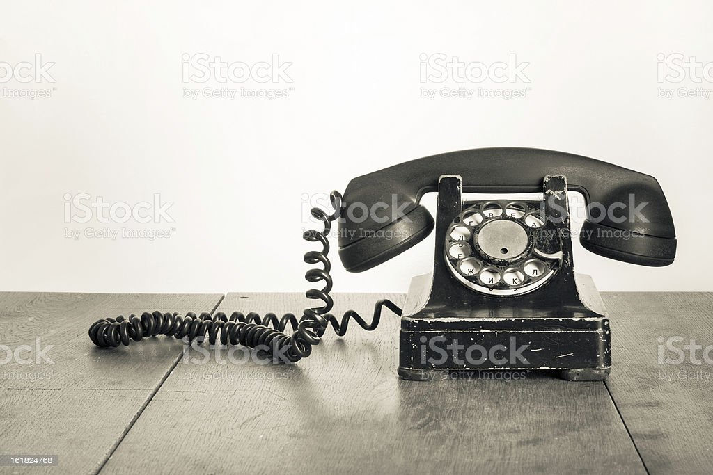 Vintage telephone on a wooden table stock photo