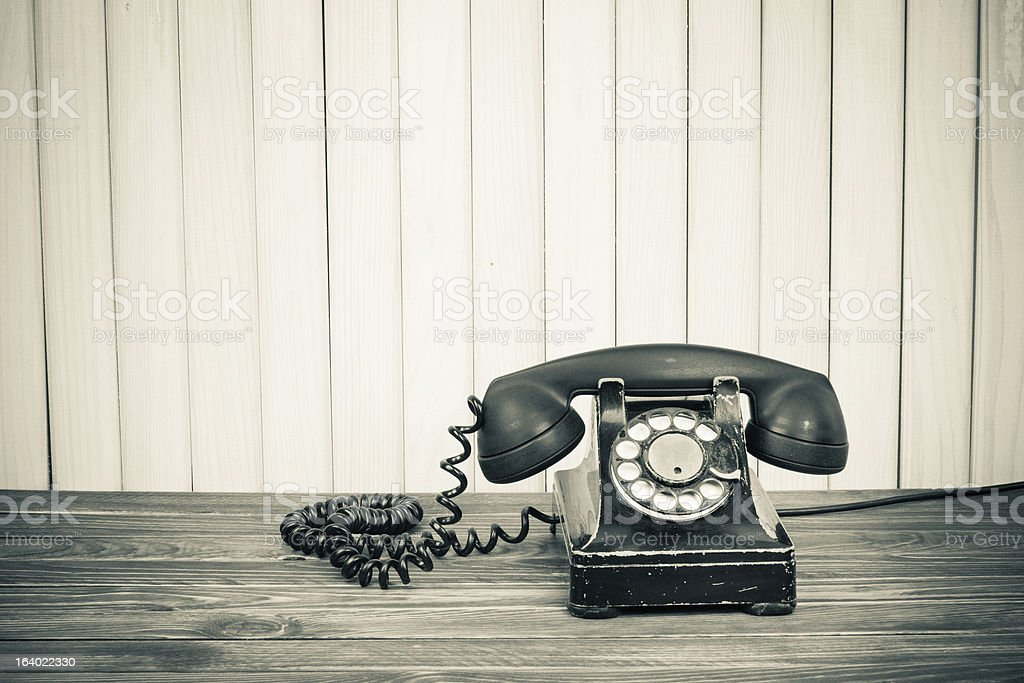 Vintage telephone on old table sepia photo stock photo