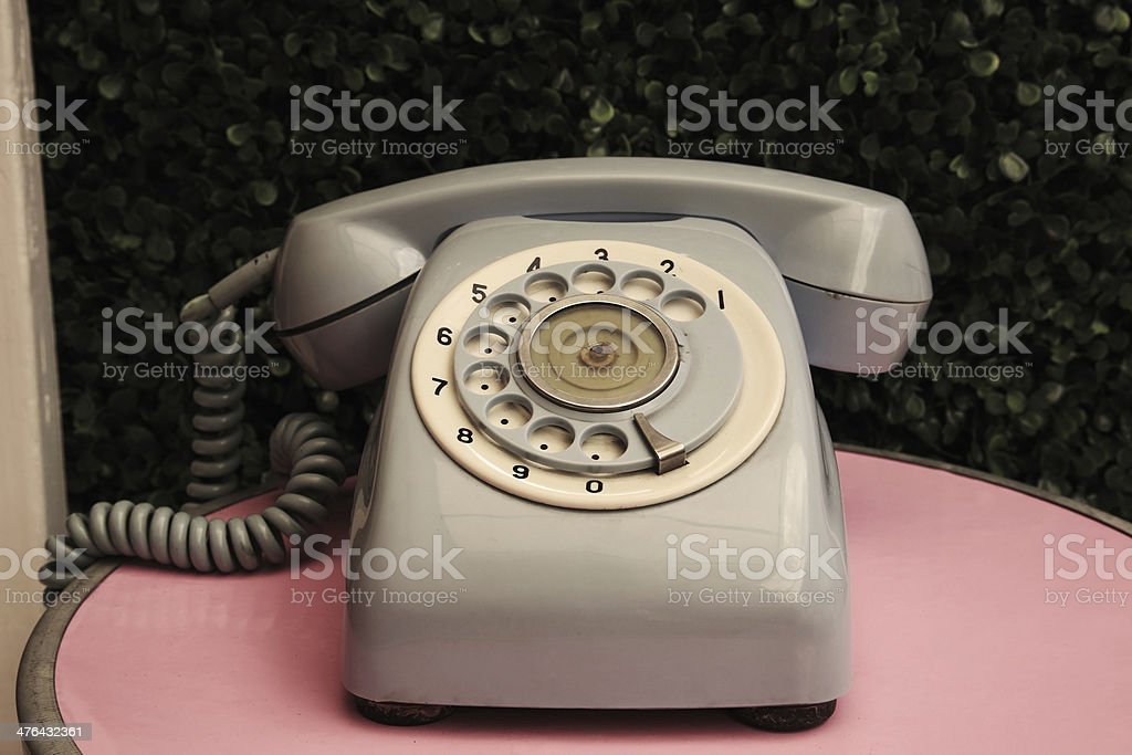 Vintage telephone on pink table royalty-free stock photo