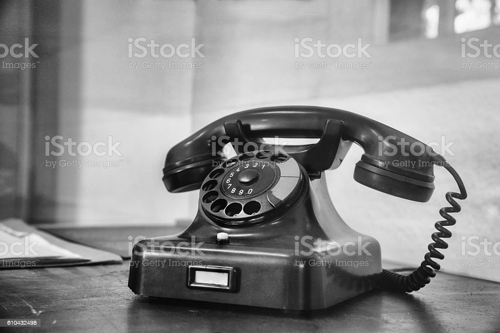 vintage telephone with dial plate on old desk stock photo