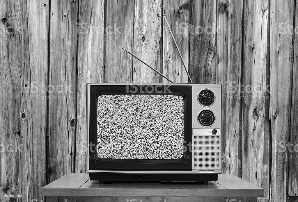 Vintage television with rustic wood wall and static screen in black...