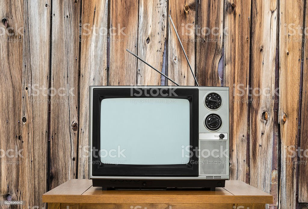 Vintage Television with Table with Rustic Wood Wall stock photo
