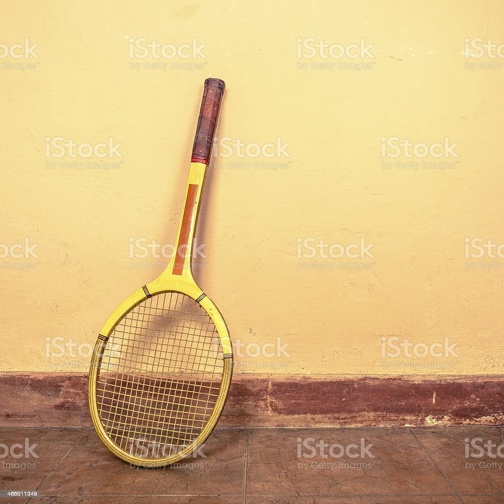 Vintage tennis racket leaning up against a wall stock photo