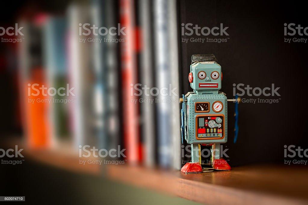 Vintage tin toy robot on a book shelf stock photo