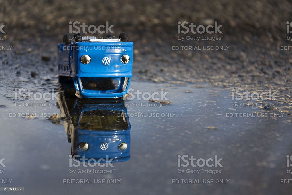 Vintage tinwork toy car with Volkswagen logo in puddle stock photo