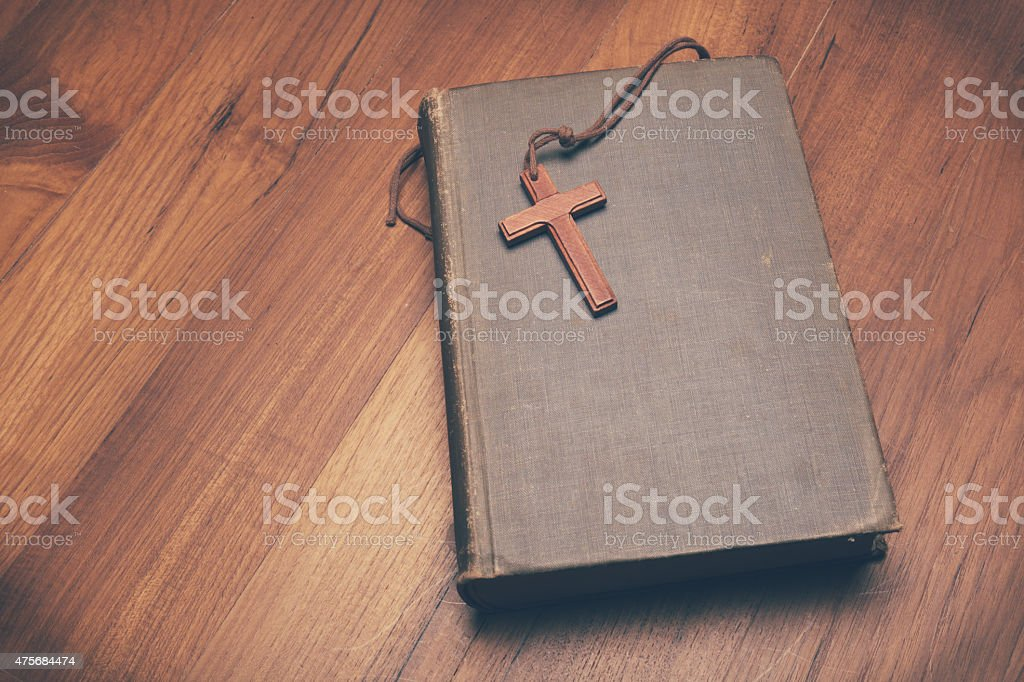 Vintage tone of wooden Christian cross necklace on holy Bible stock photo