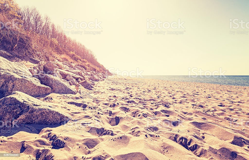 Vintage toned beach at sunset. stock photo
