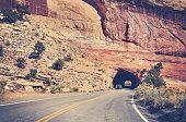 Vintage toned road through rock tunnel, Colorado, USA.