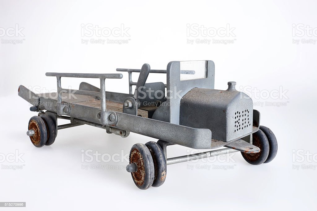 Vintage toy vehicle made of sheet metal on grey background stock photo