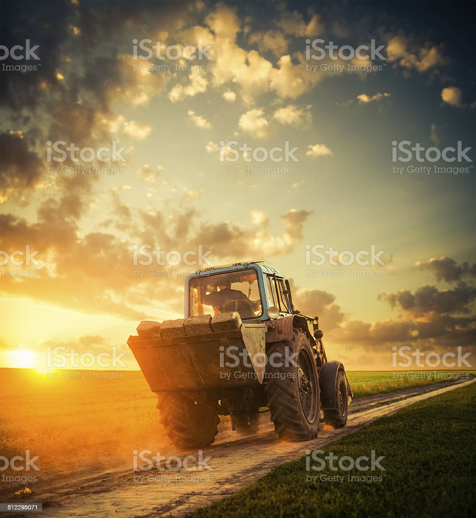 vintage tractor at rural sunset stock photo