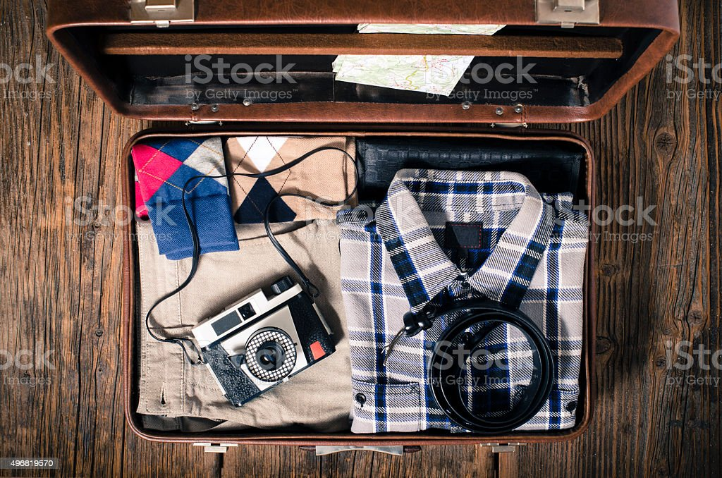 Vintage travel suitcase on wooden table stock photo