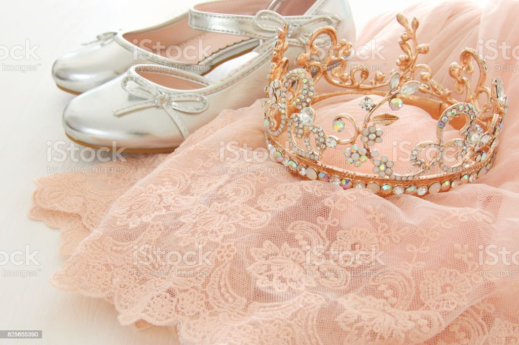 Vintage tulle pink chiffon dress, crown and silver shoes on wooden white floor stock photo